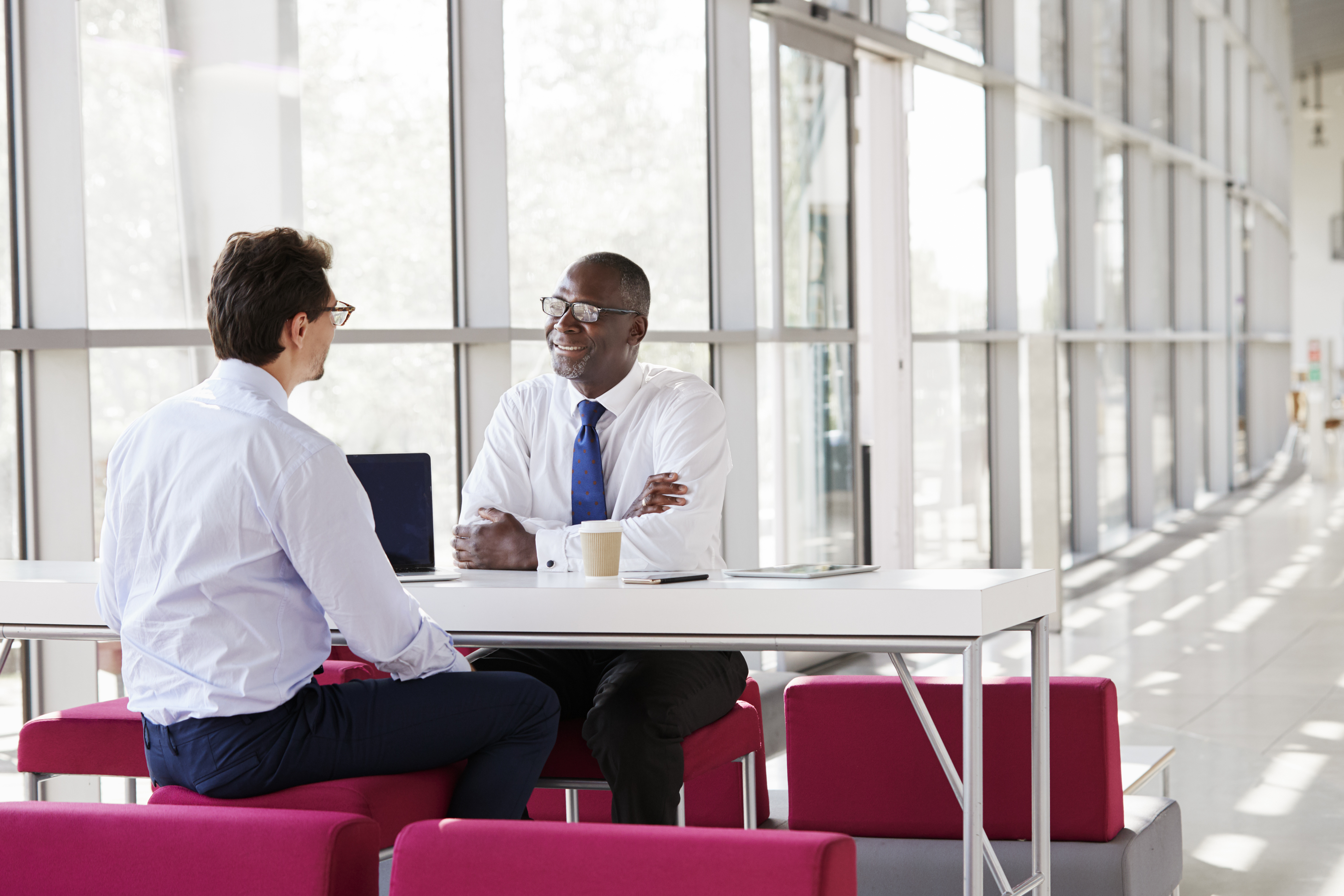 two-businessmen-talk-during-a-business-meeting-P4XYSBK